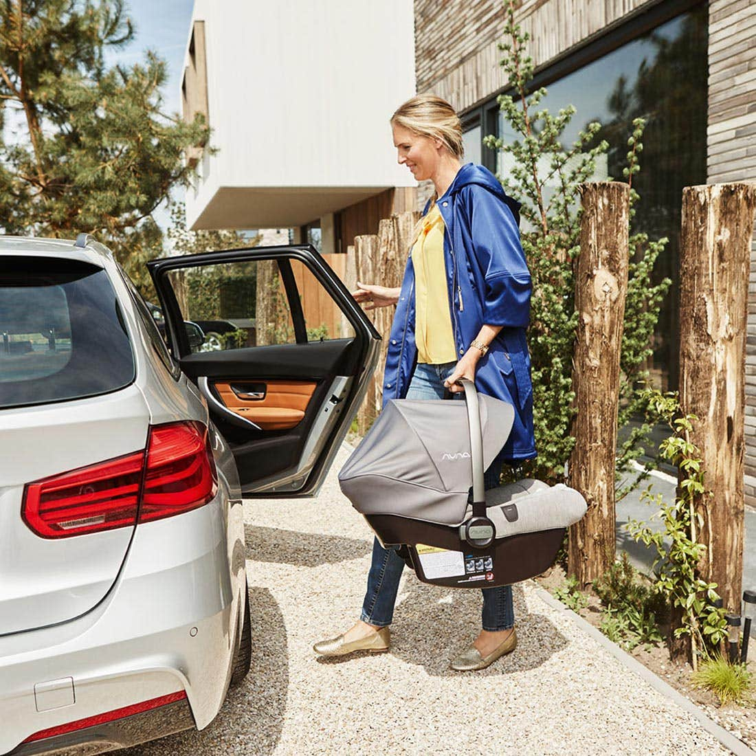 Mom carrying an infant car seat by the handle in her left hand while she opens the rear passenger-side door to put the car seat into the car.