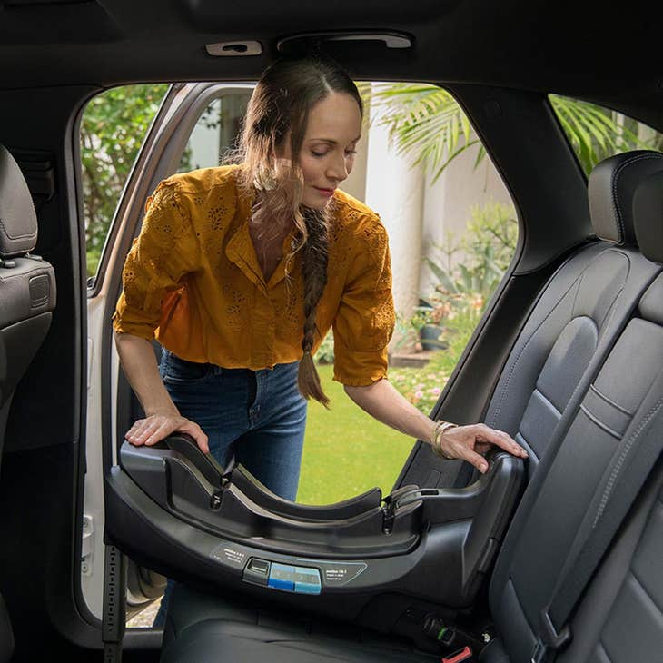 Parenting installing a rear-facing infant car seat base into the backseat of their car.