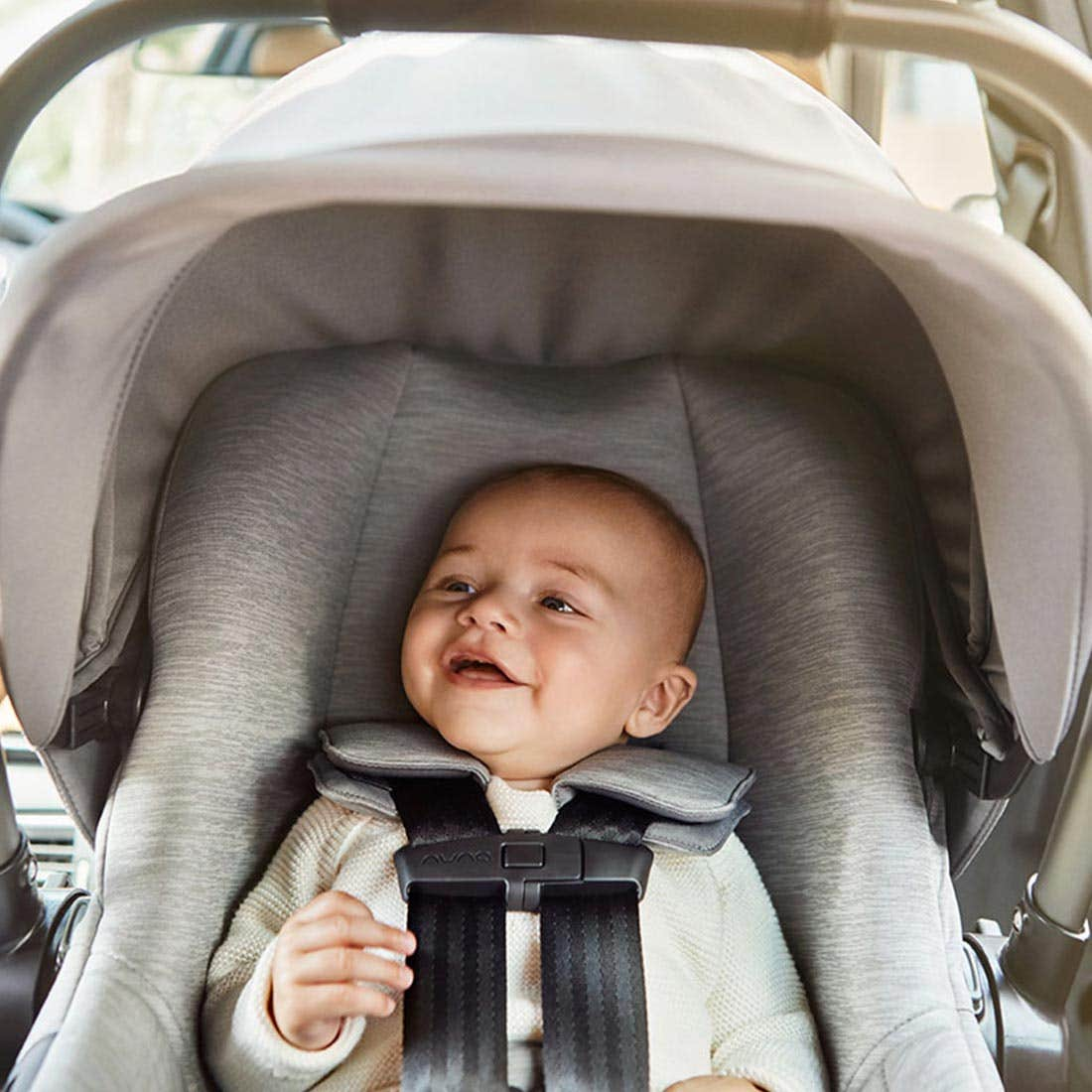 Baby smiling while buckled into a rear-facing infant car seat with canopy up, that is installed in the backseat of a car.