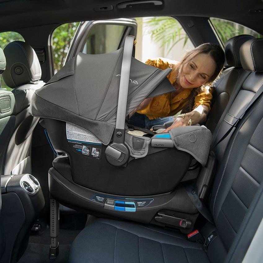 Rear-facing infant car seat with its canopy up, installed into back seat of car, mom is leaning into the car to check that baby's harness is secure.